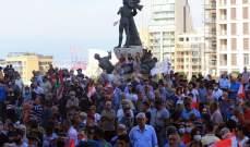 المتظاهرون بساحة الشهداء ينظمون مسيرة لوضع أكاليل الزهر مكان الإنفجار بالمرفأ