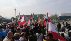 محتجون ينظمون مسيرة على طريق المطار حاملين الاعلام اللبنانية
